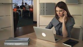 Geschäftsfrau, die an dem Laptop arbeitet und durch das Mobiltelefon im getrennten Büro spricht stock video footage