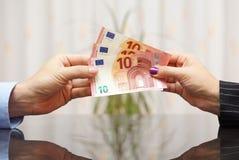 Geschäftsfrau, die dem Mann Eurobanknoten gibt Gehaltskonzept stockfotos
