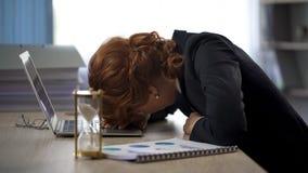 Geschäftsfrau, die den Laptop, liegend auf Tabelle, Abführung, Termindruck betrachtet stockbilder