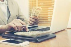 Geschäftsfrau, die den Taschenrechner zählt Geld und macht Anmerkungen verwendet Lizenzfreie Stockbilder