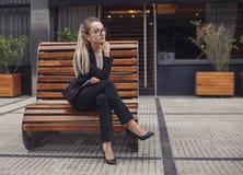 Geschäftsfrau, die an der Bank betrachtet Kamera sitzt Stockfotografie