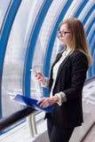 Geschäftsfrau, die in der Hand das Telefon mit einem Ordner mit Dokumenten betrachtet Stockfotografie
