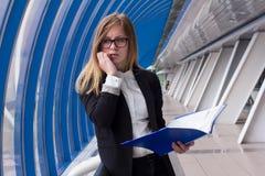 Geschäftsfrau, die in der Hand am Telefon mit einem Ordner mit Dokumenten spricht Lizenzfreie Stockfotos