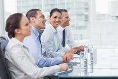 Geschäftsfrau, die an der Kamera während ihr Kollegehören lächelt Stockfotografie