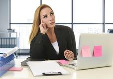 Geschäftsfrau, die an der Laptop-Computer sitzt auf dem Schreibtischabwesenden gekümmert arbeitet Stockfotos