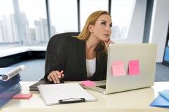 Geschäftsfrau, die an der Laptop-Computer sitzt auf dem Schreibtischabwesenden gekümmert arbeitet Stockfotografie
