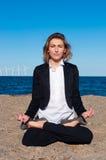 Geschäftsfrau, die in der Lotoshaltung auf dem Strand sitzt Lizenzfreie Stockbilder