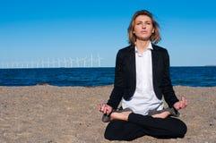 Geschäftsfrau, die in der Lotoshaltung auf dem Strand sitzt, Stockfotos