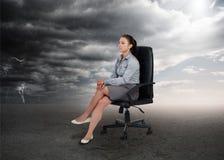 Geschäftsfrau, die in der Mitte von gegenüberliegenden Wettereinstellungen sitzt Lizenzfreies Stockbild