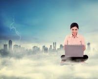 Geschäftsfrau, die an der Wolke über der Stadt arbeitet Lizenzfreies Stockbild