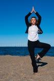 Geschäftsfrau, die in der Yogahaltung auf dem Strand steht Stockbild