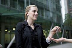 Geschäftsfrau, die der zweiten Person Metallschlüssel übergibt Lizenzfreies Stockfoto