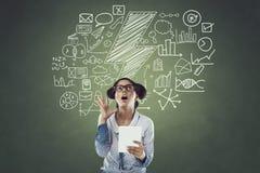 Geschäftsfrau, die digitale Tablette vor Tafel mit Ikonen verwendet Lizenzfreie Stockfotos