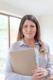 Geschäftsfrau, die Dokumente und das Lächeln hält Stockbild