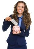 Geschäftsfrau, die 100 Dollar Banknote in Sparschwein setzt Lizenzfreie Stockbilder