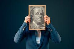 Geschäftsfrau, die Dollarporträt Benjamin Franklins 100 USA hält Lizenzfreies Stockfoto