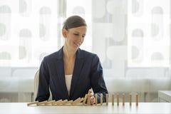 Geschäftsfrau, die Dominos am Zerbröckeln verhindert Lizenzfreie Stockbilder