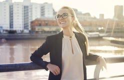 Geschäftsfrau, die draußen Fluss- und Stadthintergrund lacht Stockfotos