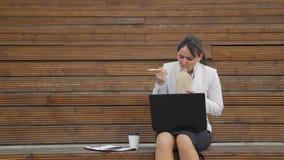 Geschäftsfrau, die draußen isst und arbeitet stock footage