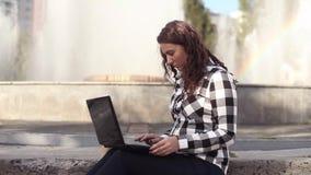 Geschäftsfrau, die draußen Laptop auf einem Bruch, schöne Studentin sitzt auf einem Brunnen verwendet stock video footage