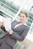 Geschäftsfrau, die draußen lesende Schreibarbeit steht Stockbilder