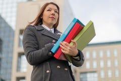 Geschäftsfrau, die draußen Ordner mit Dokumenten hält Lizenzfreies Stockbild