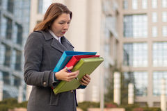 Geschäftsfrau, die draußen Ordner mit Dokumenten hält Stockbild