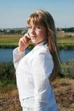 Geschäftsfrau, die durch Handy benennt Stockbild