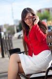 Geschäftsfrau, die durch Telefon, tragende rote Jacke benennt Stockbilder