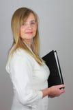 Geschäftsfrau, die ein Aktenfaltblatt trägt Lizenzfreies Stockfoto