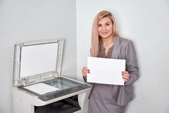 Geschäftsfrau, die ein Blatt Papier hält und Kamera betrachtet stockfoto
