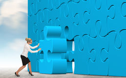 Geschäftsfrau, die ein blaues Puzzlespiel auf einem Himmelhintergrund aufbaut Stockfotografie