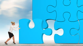 Geschäftsfrau, die ein blaues Puzzlespiel auf einem Himmelhintergrund aufbaut Lizenzfreies Stockbild