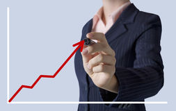 Geschäftsfrau, die ein Diagramm auf Schirm zeichnet Lizenzfreie Stockbilder