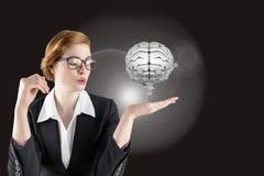 Geschäftsfrau, die ein digitales Gehirn mit schwarzem Hintergrund hält Stockbild