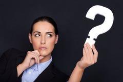 Geschäftsfrau, die ein Fragezeichen anhält Lizenzfreie Stockfotos