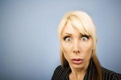 Geschäftsfrau, die ein lustiges Gesicht bildet Stockbild