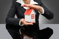 Geschäftsfrau, die ein Musterhaus hält Lizenzfreies Stockfoto