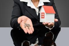 Geschäftsfrau, die ein Musterhaus und einen Schlüssel hält Lizenzfreie Stockfotos