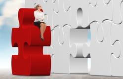 Geschäftsfrau, die ein Puzzlespiel auf einem Himmelhintergrund aufbaut Lizenzfreie Stockbilder