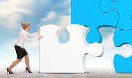 Geschäftsfrau, die ein Puzzlespiel auf einem Himmelhintergrund aufbaut Stockfoto