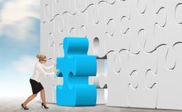 Geschäftsfrau, die ein Puzzlespiel auf einem Himmelhintergrund aufbaut Stockfotografie