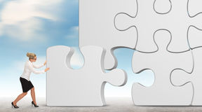Geschäftsfrau, die ein Puzzlespiel auf einem Himmelhintergrund aufbaut Lizenzfreies Stockbild