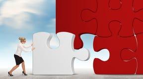Geschäftsfrau, die ein Puzzlespiel auf einem Himmelhintergrund aufbaut Stockbilder