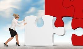 Geschäftsfrau, die ein Puzzlespiel auf einem Himmelhintergrund aufbaut Stockfotos