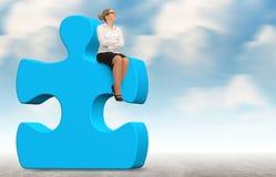 Geschäftsfrau, die ein Puzzlespiel auf einem Himmelhintergrund aufbaut Lizenzfreie Stockfotos