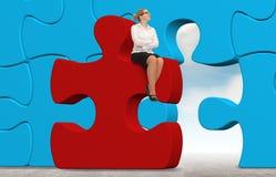 Geschäftsfrau, die ein Puzzlespiel auf einem Himmelhintergrund aufbaut Lizenzfreie Stockfotografie