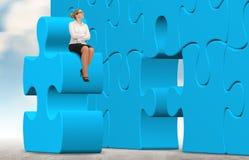 Geschäftsfrau, die ein Puzzlespiel auf einem Himmelhintergrund aufbaut Lizenzfreies Stockfoto