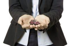 Geschäftsfrau, die ein Spielzeugauto darstellt Stockbilder