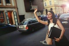 Geschäftsfrau, die ein Taxi fängt lizenzfreie stockfotografie